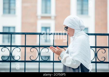 Une jeune femme musulmane priant en plein air dans le hijab blanc. Vue latérale.