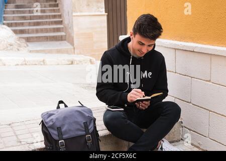 Joyeux jeune homme dans des vêtements décontractés à l'écoute de la musique ecouteurs et écriture dans un ordinateur portable en étant assis sur un pied près sac à dos sur la rue de la ville Banque D'Images