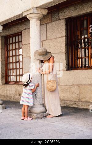 Vue latérale d'une femme méconnue sous un chapeau et d'un enfant debout sur le trottoir le long de la vieille maison sur la colonne