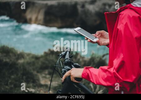 Vue rapprochée de la main d'une femme anonyme sur la navigation à vélo téléphone portable