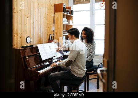 Jeune homme apprenant à jouer du piano près d'une femme noire enseignante en studio de musique