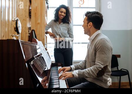 Jeune homme apprenant à jouer du piano près de la femme noire enseignant en studio de musique