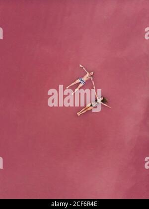 Vue aérienne de l'homme et de la femme paisibles dans les maillots de bain tenant mains tout en flottant sur l'eau salée rose du lac à Torrevieja en Espagne Banque D'Images