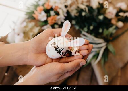 jeune femme tenant un oeuf de pâques avec des oreilles de lapin peintes par les enfants avec des fleurs