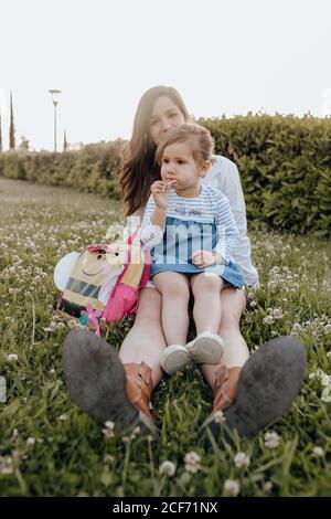 Jeune femme gaie et petite fille avec le Lollipop assis sur herbe verte près du sac à dos tout en passant du temps dans le parc ensemble Banque D'Images