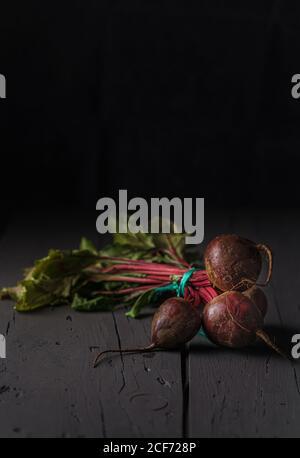 Du dessus des betteraves à sucre rouge foncé sur la tige avec du vert feuilles sur fond noir Banque D'Images