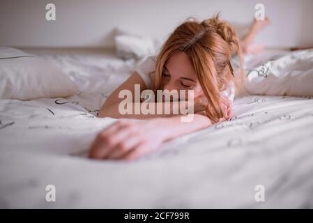 Jeune femme satisfaite avec un crayon dans les cheveux rouges ayant le repos après un réveil le matin du week-end et à la maison couché sur l'estomac sur un lit confortable avec du linge blanc et souriant avec fermé yeux