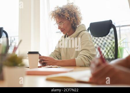 Femme d'affaires mûre utilisant son téléphone mobile tout en étant assise au table pendant la réunion au bureau
