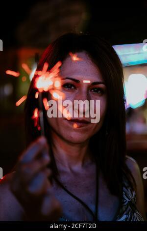 Portrait du contenu femme tenant le sparkler regardant l'appareil photo allumé arrière-plan flou du parc d'attractions dans l'obscurité Banque D'Images