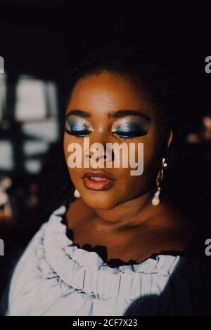 Portrait de rétro-éclairé beau curvy noir jeune femme avec lumineux maquillage dans la robe hors-épaule en regardant vers le bas