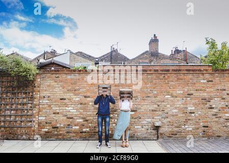 Couple en tenue décontractée debout près du mur de briques dans la ville et mettre des boîtes de fruits en bois sur les têtes tout en se comportant ridiculement