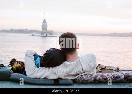 Vue arrière d'un couple amoureux anonyme qui s'enserre assis sur des oreillers sur le front de mer et profiter d'un merveilleux coucher de soleil pendant la romantique date à l'intérieur Istanbul Banque D'Images