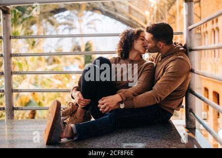 Joyeux jeune homme et femme embrassant et embrassant regarder les uns les autres en étant assis dans un pavillon éclairé pendant la date