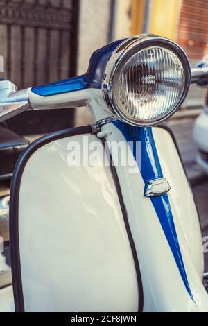 Scooter à moteur rétro blanc et bleu avec phare rond en position de stationnement sur la rue de la ville