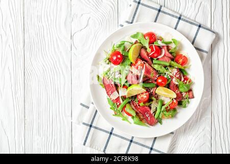 Salade de steak de bœuf de steak d'aloyau en tranches avec des arugula, des tomates cerises, des haricots verts, du parmesan râpé servi sur une assiette blanche avec des quartiers de citron vert Banque D'Images