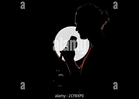 Vue latérale d'un musicien de sexe masculin chantant dans le microphone dans l'obscurité studio avec lampe éclairée