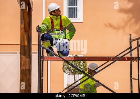 Ingénieur professionnel en uniforme et casque assis sur un échafaudage et regarder loin en travaillant avec un collègue sur l'entretien de l'électricité équipement près du bâtiment résidentiel