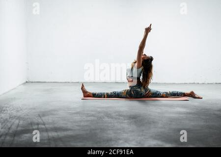 Vue latérale de la jeune femme flexible dans les vêtements de sport faisant devant séparer avec les bras relevés en étant assis sur le plancher