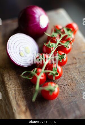 Bouquet de tomates mûres fraîches cerise et oignon rouge coupé ampoules placées sur une planche à découper en bois Banque D'Images