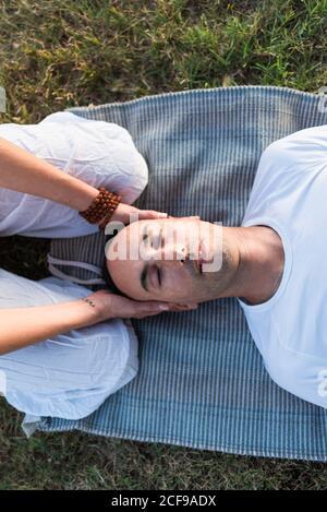 couple calme méditant tandis que l'homme allongé sur le tapis avec les yeux fermé et femme assise sur les genoux et tenant partenaire par dirigez-vous vers le bas dans la prairie verte