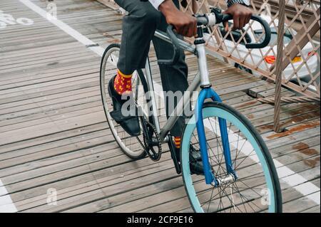 Court anonyme bien habillé homme d'affaires cycliste dans l'équitation sur le vélo Route en bois parmi la structure en métal rouge avec à New York ville