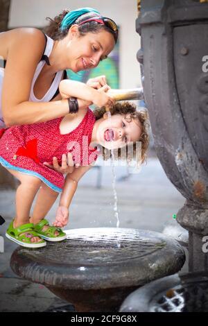 Bonne mère versant de l'eau de la fontaine de boisson pour fille drôle avec ouverture sur la rue en été Banque D'Images