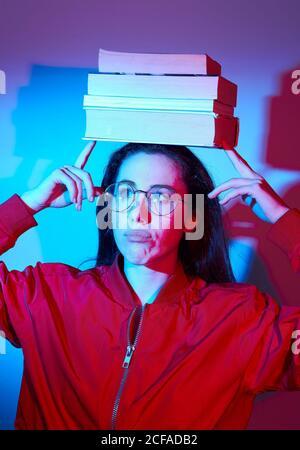 Femme grimaçant dans une veste rouge décontractée et pile d'équilibrage de lunettes de livres sur la tête tout en restant dans la lumière bleue studio donnant sur l'extérieur Banque D'Images