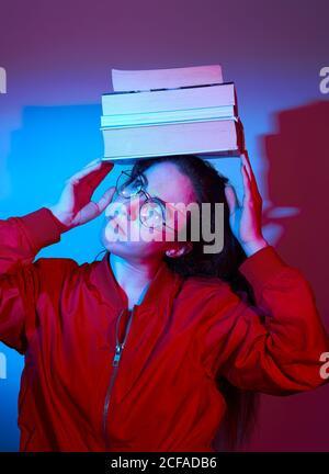 Femme grimaçant dans une veste rouge décontractée et pile d'équilibrage de lunettes de livres sur la tête tout en restant dans la lumière bleue studio Banque D'Images