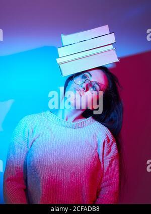 Grimaçant la femme en tenue décontractée et lunettes équilibrant pile de livre sur la tête en étant debout dans un studio à la lumière bleue vue sur l'extérieur Banque D'Images