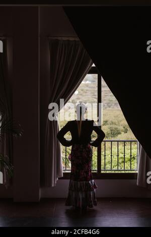Danseuse en costume pour le flamenco se tenant et regardant dehors fenêtre Banque D'Images