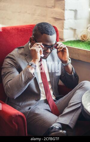 Portrait d'un jeune homme d'affaires afro-américain confiant et réussi portant des lunettes élégantes et un élégant costume sombre habillé sourire heureux, réjouissez-vous