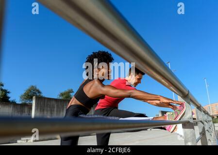 D'en-dessous de la vue latérale de la joyeuse African American fitness femme et souriant homme sportif debout à côté de la clôture en métal et étirez vos jambes tout en vous formant ensemble par temps ensoleillé avec du bleu ciel en arrière-plan