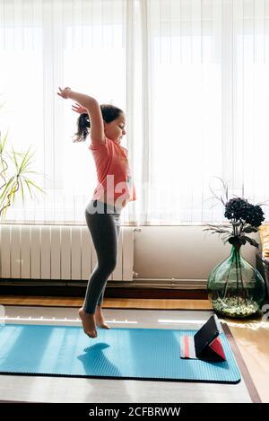 Vue latérale de la femme enfant en coupe décontractée sautez sur le tapis contre la fenêtre à la maison tout en faisant du yoga et regarder des didacticiels vidéo sur tablette