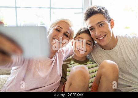 Mère avec ses deux fils emportant le selfie à la maison Banque D'Images