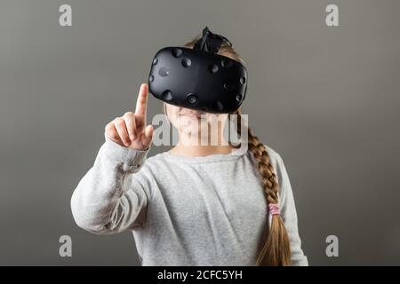 Une fille s'y porte avec un appareil VR et touche le doigt air