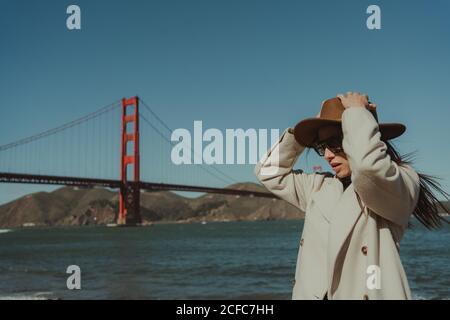 Vue latérale d'une jeune femme avec chapeau et tenue tendance Et des lunettes de soleil se tenant sur le remblai contre le pont du Golden Gate dedans Californie en journée ensoleillée