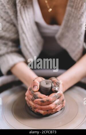 potter femelle anonyme avec des mains sales faisant pot d'argile sur roue dans l'atelier