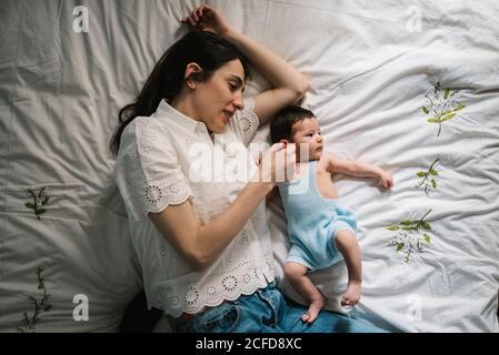 Belle femme adulte touchant doucement bébé doux tout en étant couché lit confortable