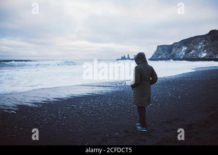 Une femme donne sur la mer sur Black Sand Beach à Vik et Myrdal