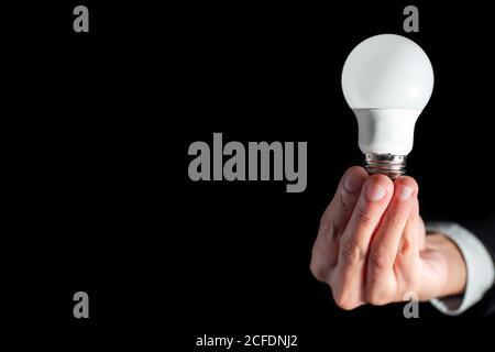 un homme d'affaires prospère tient l'ampoule technologique pour réussir la pensée créative d'entreprise concept d'idée avec combinaison pendant le travail au bureau et l'innovation succrez Banque D'Images