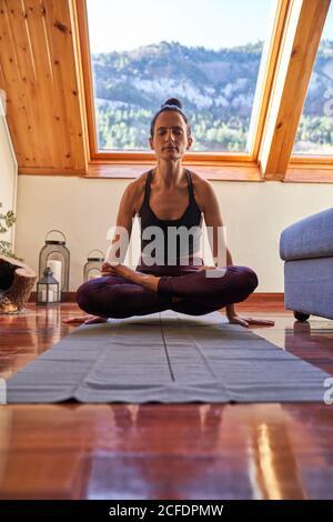 Femme mince avec les yeux fermés assis soulevant son corps de le sol s'est croisé pendant l'entraînement de yoga méditant à accueil