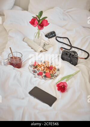 De dessus plat avec de délicieuses gaufres et baies fraîches sur le lit avec appareil photo, livre et téléphone