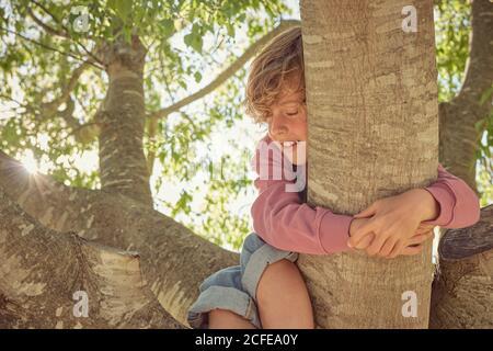 Enfant plein d'énergie souriant avec les yeux fermés arbre d'escalade et de tenue sur le coffre