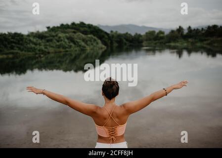Vue arrière de la jeune femme avec bras étirés à proximité étang calme et profiter de la liberté dans la campagne