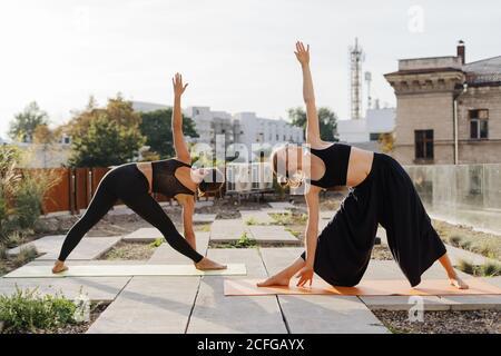 Deux jeunes filles qui pratiquent le yoga et stretching exercice d'entraînement ensemble sur la terrasse