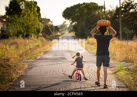 Petite fille, à vélo, avec son jeune père portant une grosse citrouille d'halloween sur sa tête, sur une route de campagne au coucher du soleil. Vue arrière.