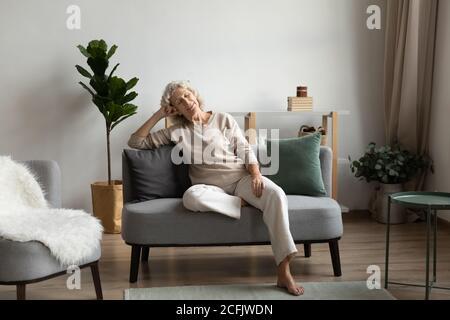 Femme calme et mature assise, reposant sur un canapé confortable à la maison