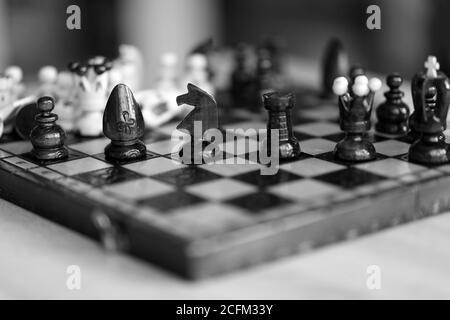 Pièces d'échecs sur plateau de jeu en bois de couleur noire et blanche. Les pièces comprennent le pion, le roi, la reine, l'évêque, le chevalier et le rook.