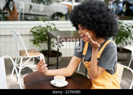 Bonne femme africaine parlant de passer un appel vidéo au téléphone à la table du café extérieur. Banque D'Images