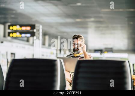 Un homme de race blanche adulte travaille sur un ordinateur portable qui l'attend vol à la porte de l'aéroport - concept de nomade numérique et de la technologie liée à l'emploi - pe moderne